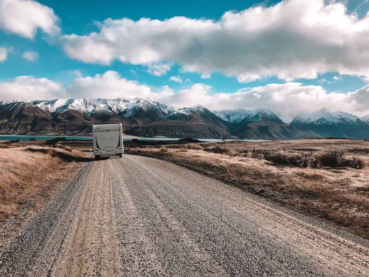 campervan driving along dirt road in new zealand
