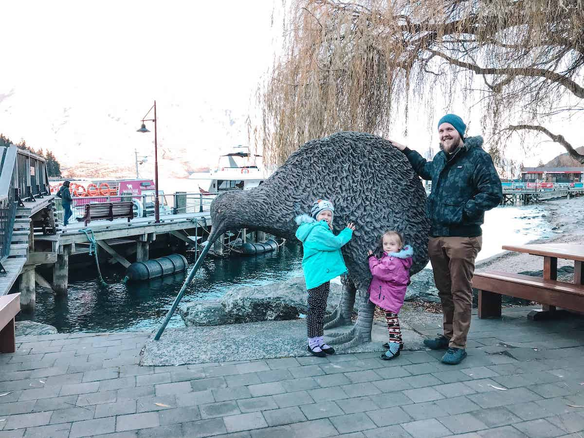 family in queenstown with giant kiwi statue