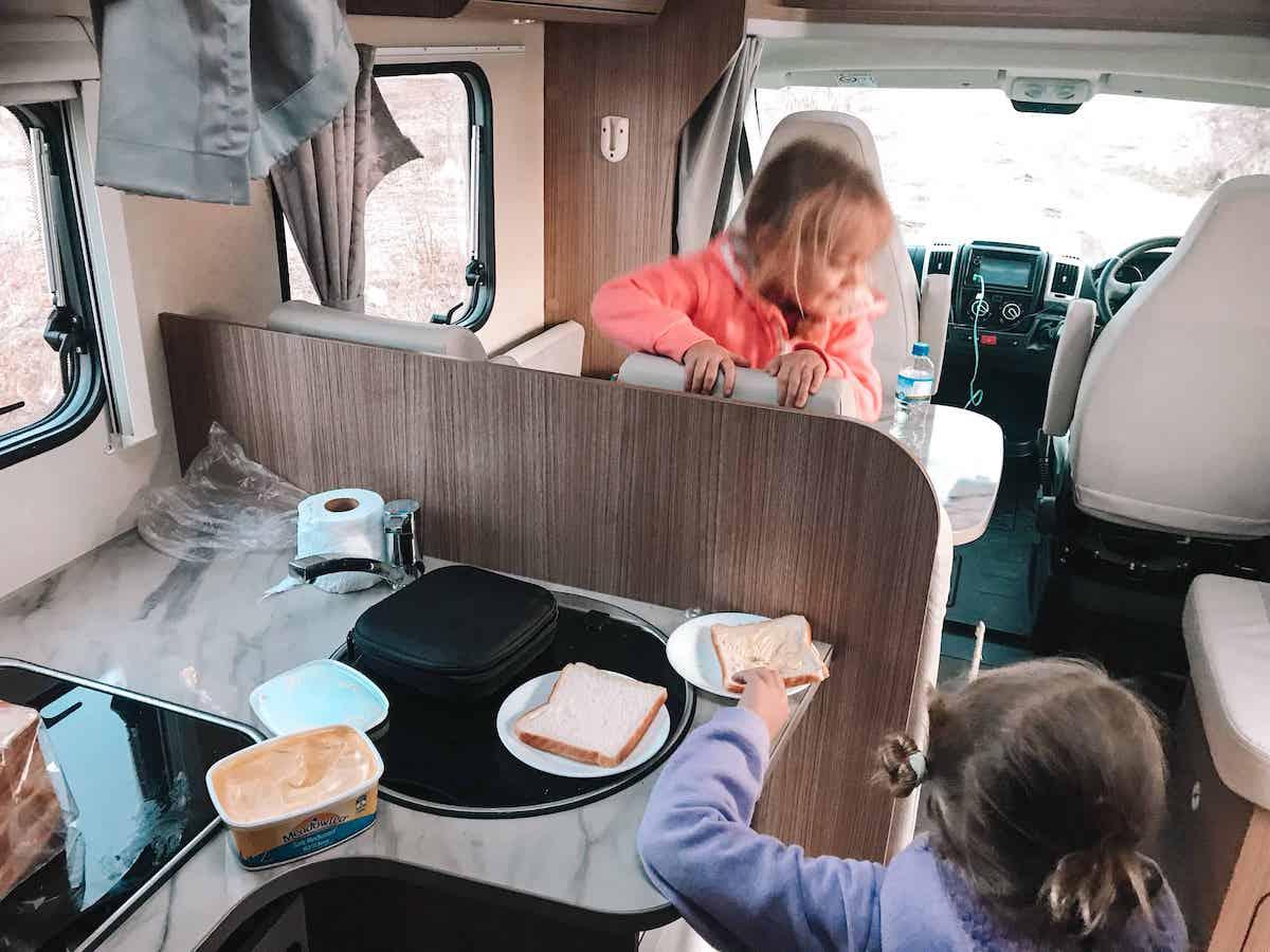 kids making breakfast in campervan