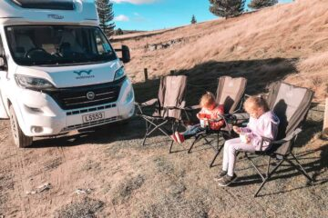 kids on camp chairs next to campervan