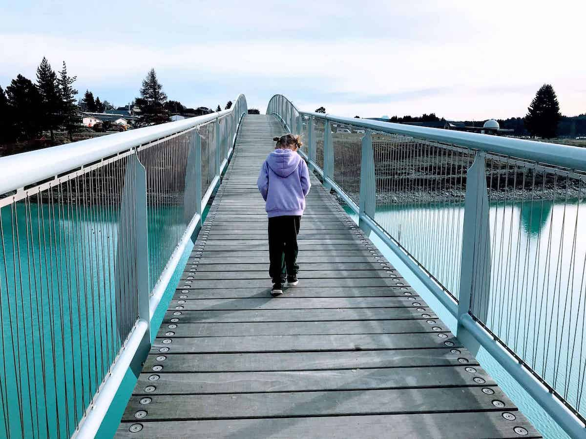 child crossing over lake tekapo footbridge