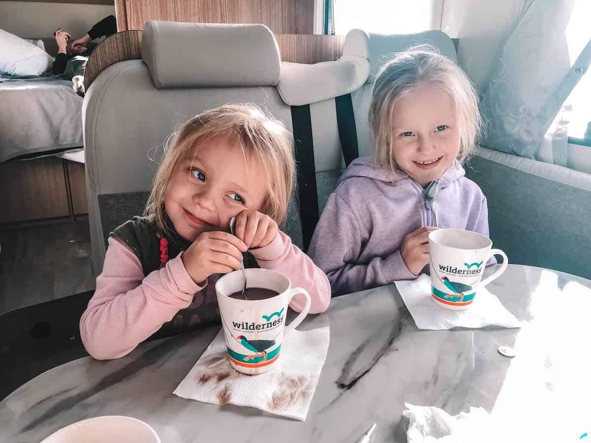 kids in campervan having hot chocolate