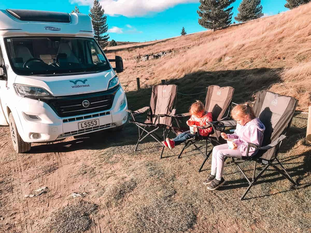 Motorhome at campsite with chairs