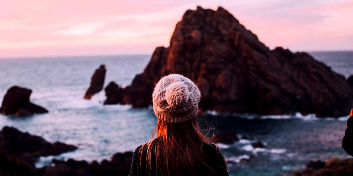 woman at sunset looking out to ocean