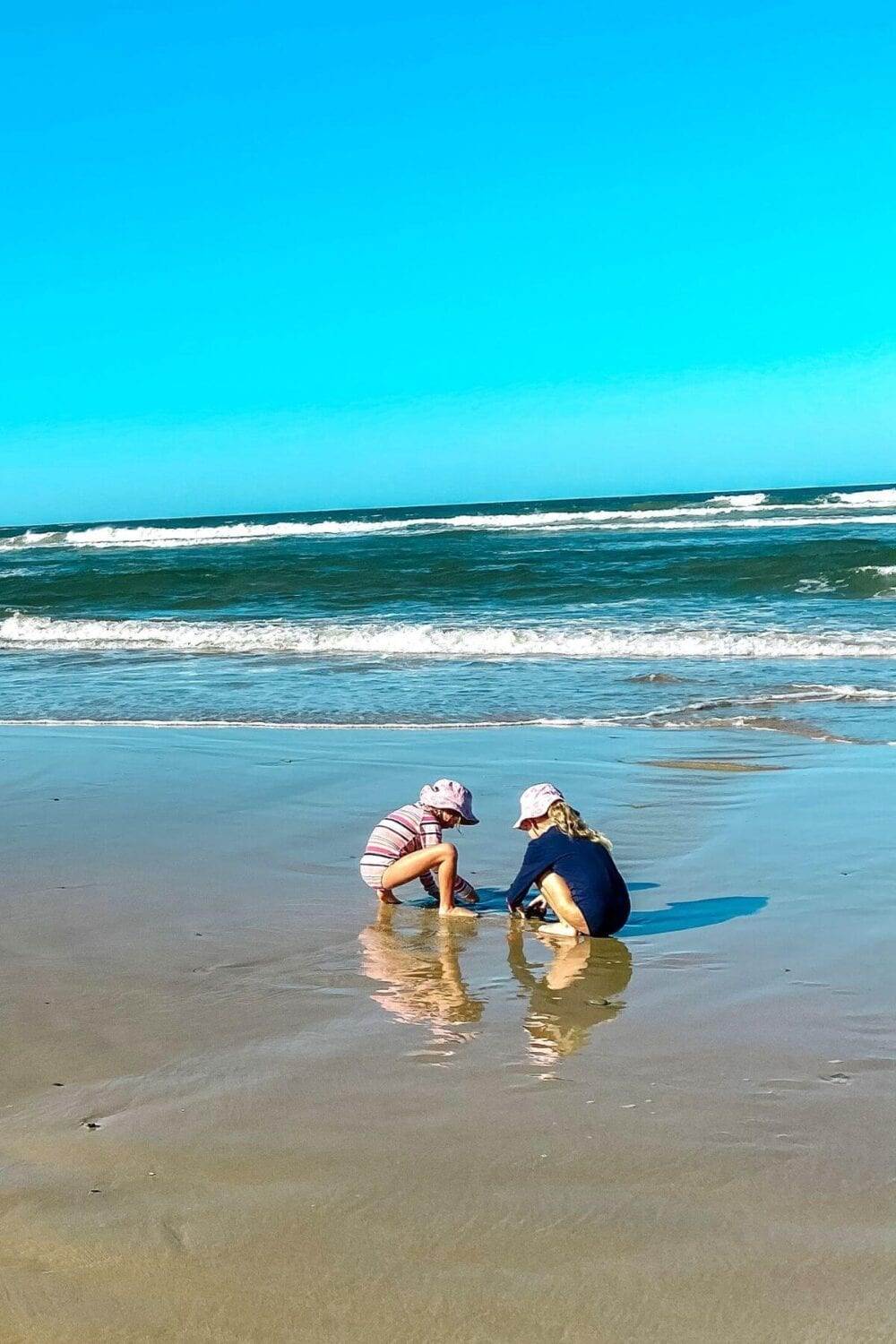 kids playing at the beach in sun protective clothing