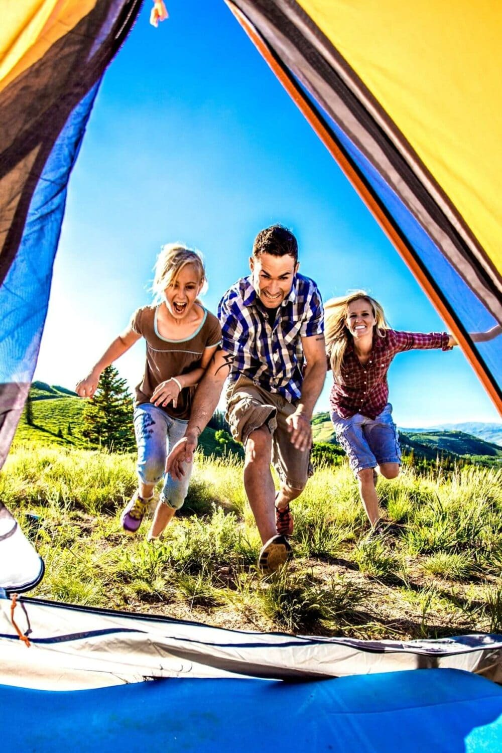 family racing towards tent while camping