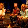 family playing fun camping game around campfire
