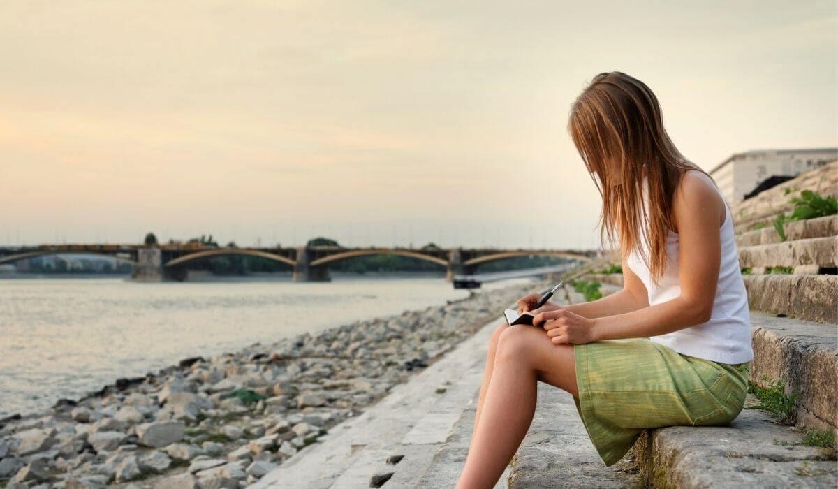 woman writing in journal by ocean