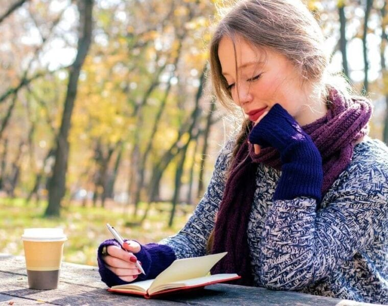 woman writing in travel journal