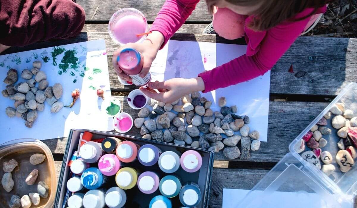 child rock painting while camping